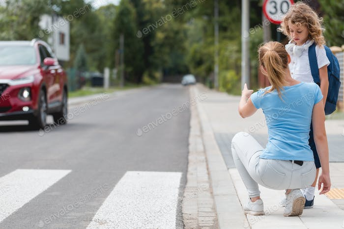 Young mother squats on the sidewalk and explains to the little boy how to cross the street safely