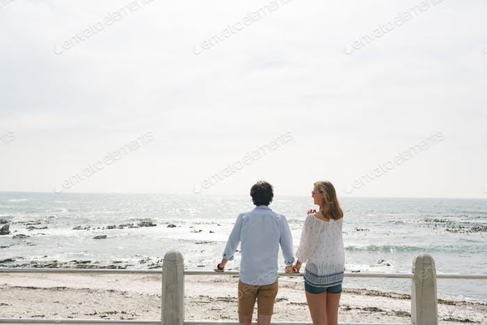 Rear view of young Caucasian couple standing hand in hand near sea side at promenade on a sunny day