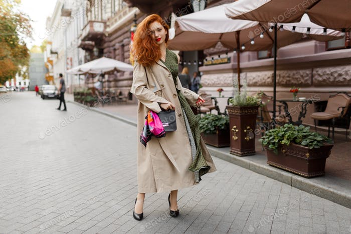 graceful ginger woman in trendy beige coat and elegant dress walking outdoor.
