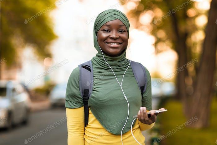 Joyful african islamic woman listening music outdoors with smartphone and earphones