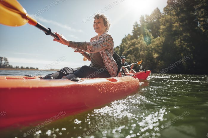 Senior woman canoeing in lake on a summer day