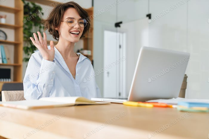 Beautiful young businesswoman sitting at the office desk