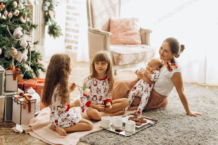 Mother with a baby on her hands sits o the carpet with her two daughters dressed in pajamas eating