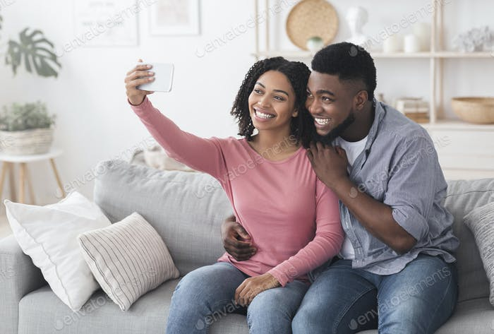 Quarantine Selfie. Smiling black couple taking photo on smartphone at home