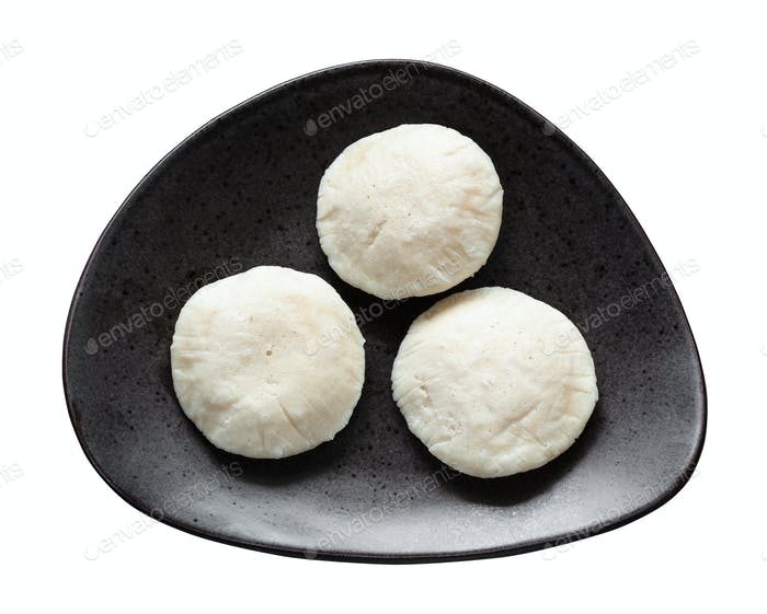 Idli Sambar dumplings on black plate isolated