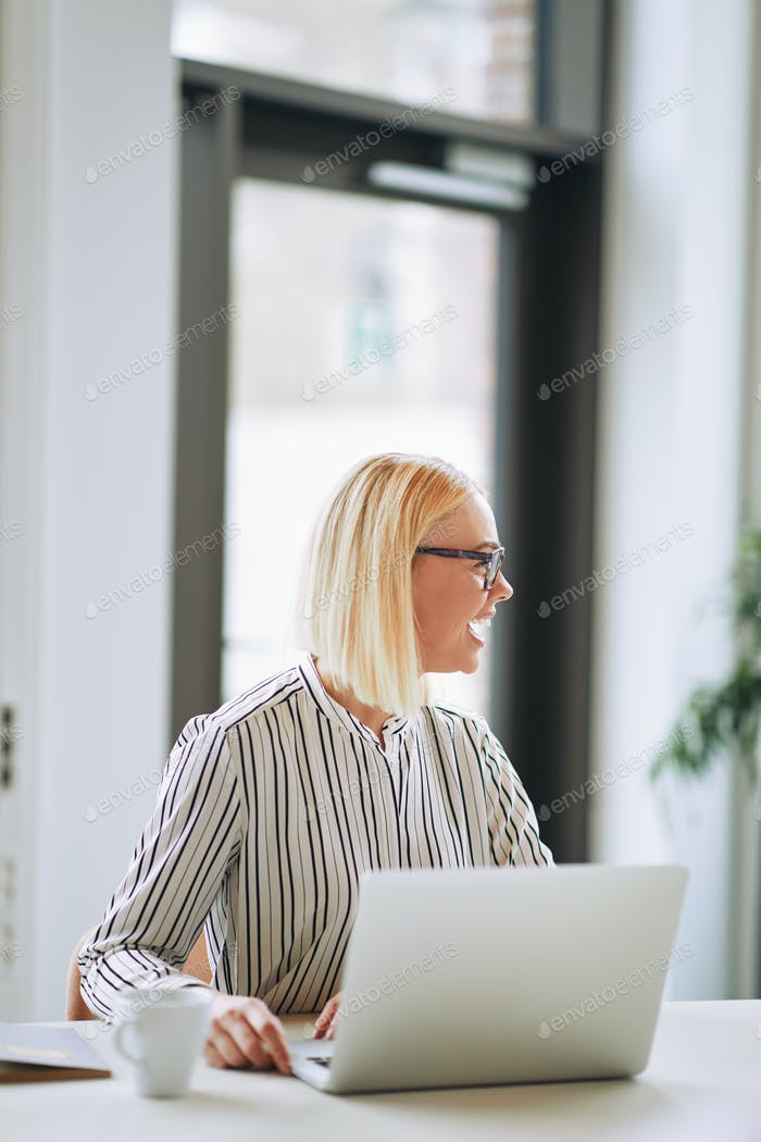 Young businesswoman laughing while working on a laptop