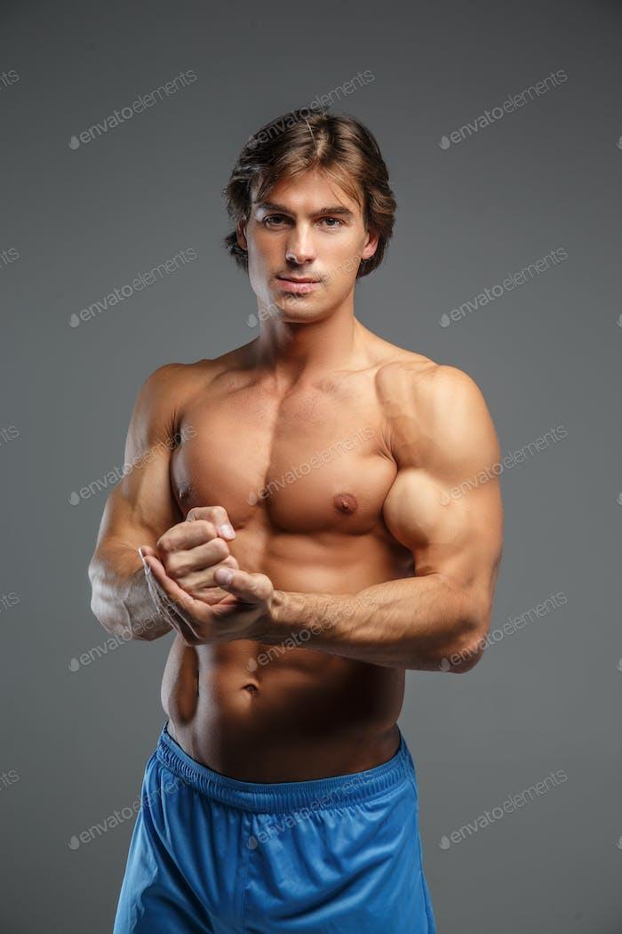 Half body portrait of muscular guy in blue shorts.