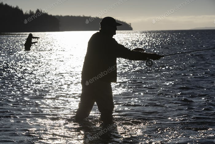 A silhouette of two fly fishermen standing in salt water while fly fishing for searun coastal