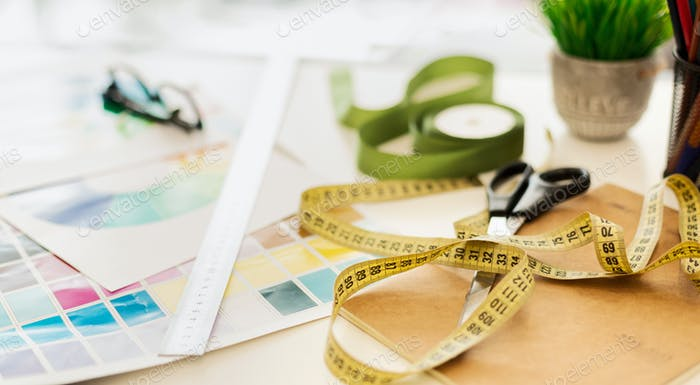 Closeup Of Fashion Designer Workplace With Measuring Tape And Color Samples
