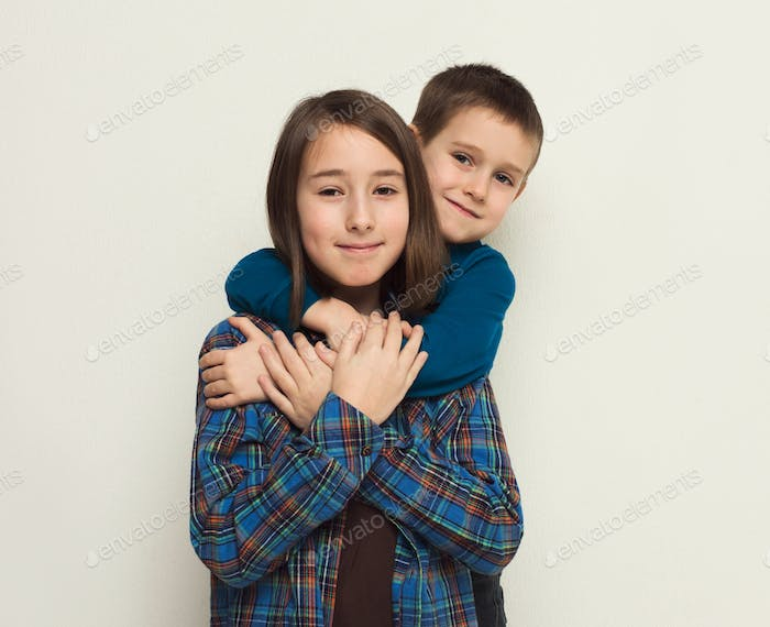 Happy brother and sister, studio background