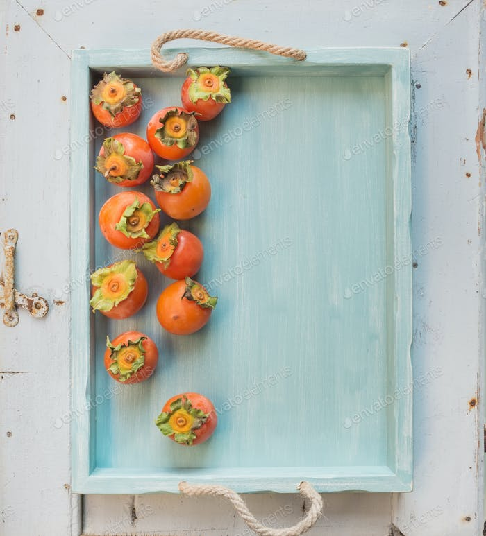 Ripe fresh persimmons on blue wooden tray over light backdrop, top view