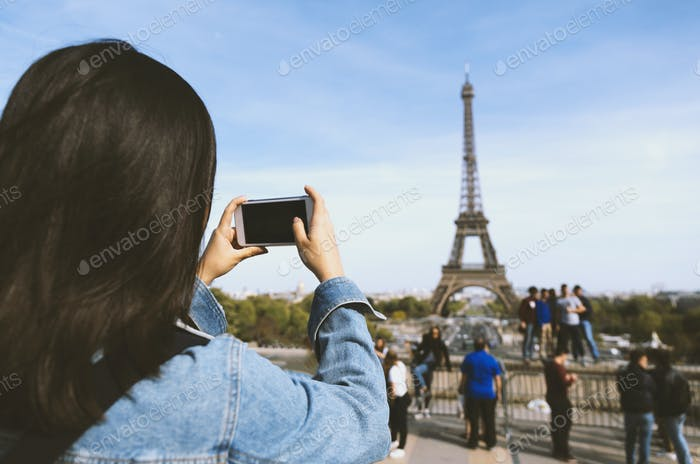 Woman tourist taking photo by phone near the Eiffel tower in Paris under sunlight and blue sky