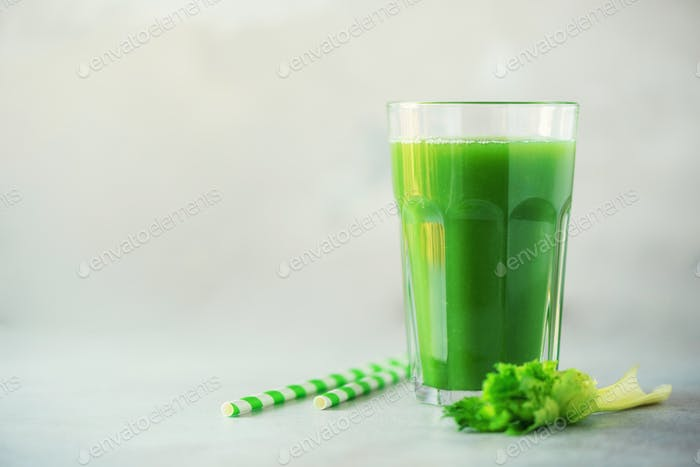 Glass of green celery smoothie on grey concrete background. Banner with copy space. Fresh juice for