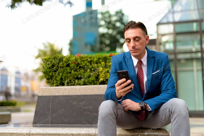 Mature handsome Italian businessman relaxing outside of the building