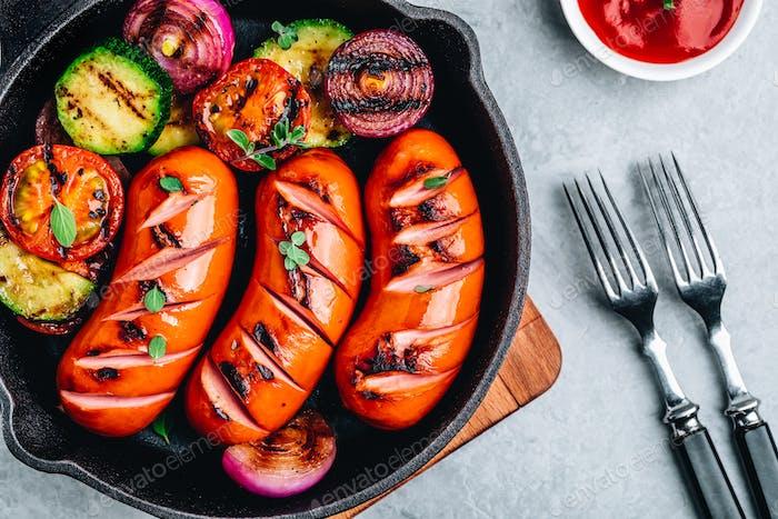 Gegrillte Würstchen und Gemüse in Gusseisenpfanne.