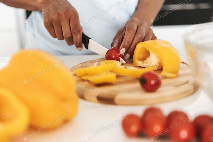 Close up of a afro american woman chopping vegetables