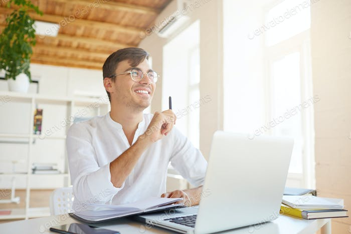 young businessman wears white shirt and spectacles with laptop and mobile phone thinking and writing