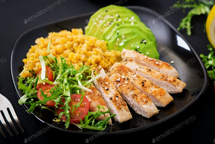 Healthy dish with chicken, tomatoes,  avocado, lettuce and lentil on dark  background. Dinner