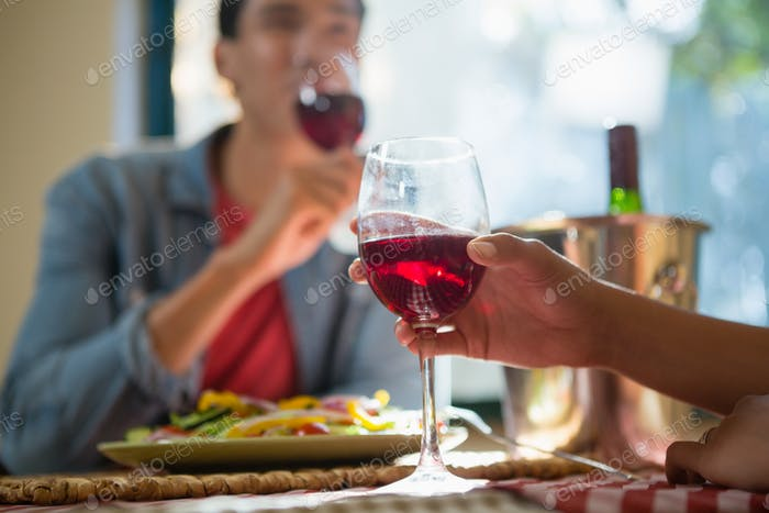 Cropped hand of woman with friend holding wineglass