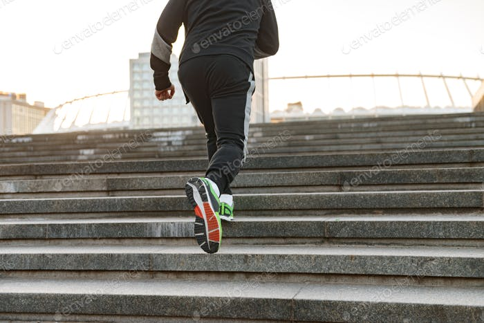 Back view of a sportsman running up the stairs