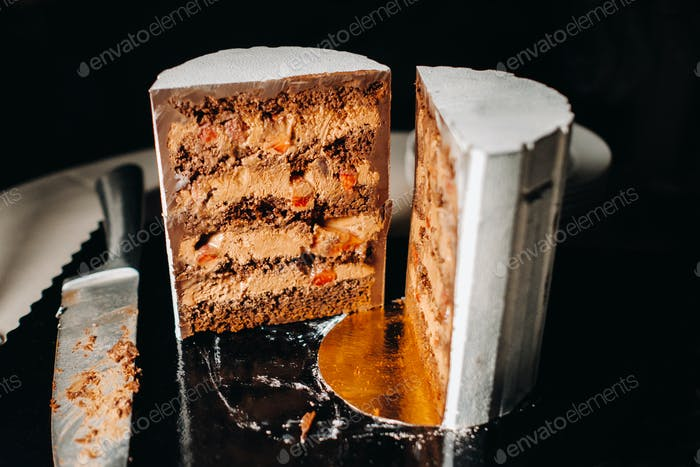 Amazing Cakes. Sliced chocolate wedding cake cake with amazing filling on a black background.Large