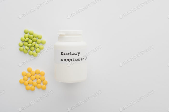 Top View of Container With Dietary Supplements Lettering And Colorful Pills on White Background