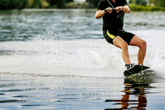 Male wakeboarder rides on lake