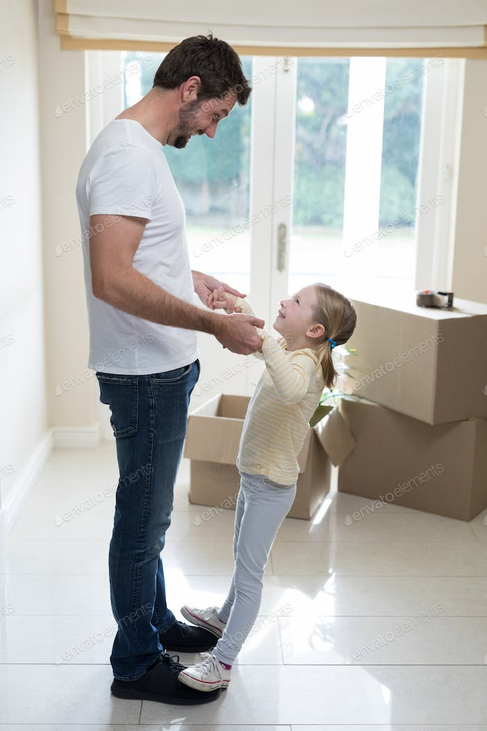 Father and daughter having fun in living room