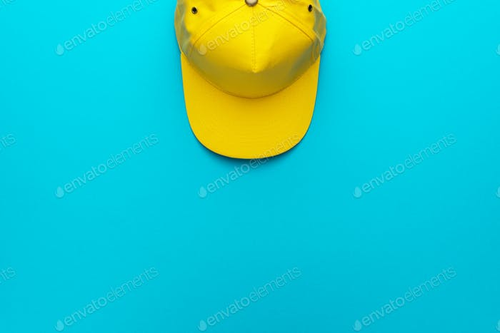 Top View Of Yellow Baseball Cap Over Blue Torquoise Background With Copy Space