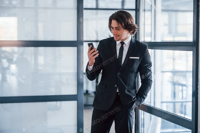 Using the phone. Portrait of handsome young businessman in black suit and tie