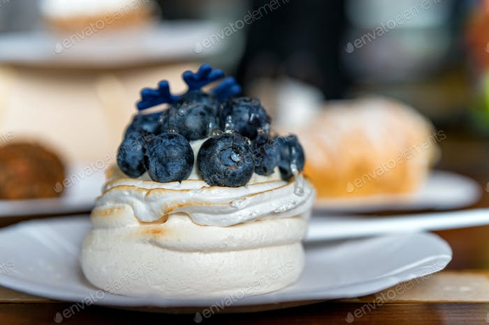 Close up meringue cake decorated with blue berry. Dessert