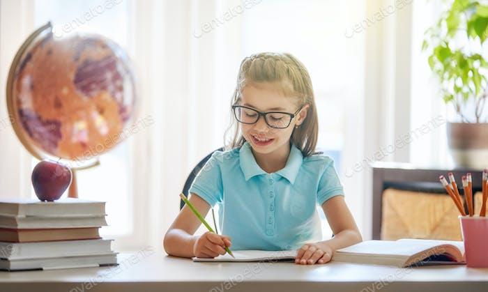 Kind sitzt an einem Schreibtisch drinnen