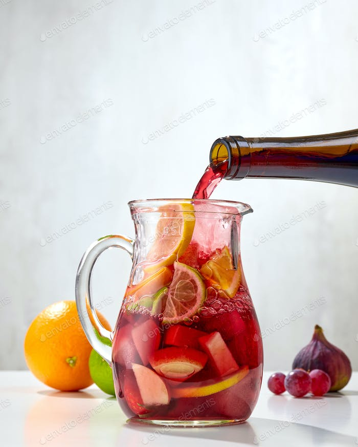 red wine pouring into jug of cutted fruits