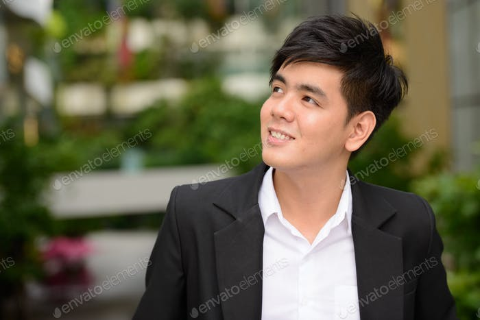 Face of happy young Asian businessman thinking at the park