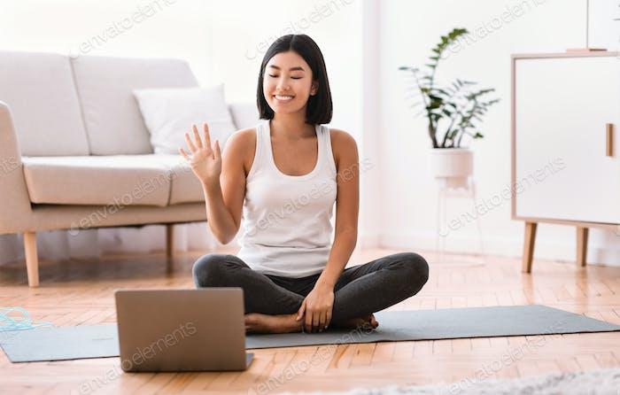 Sportliche asiatische Frau winkt zu Laptop, Heimtraining Konzept