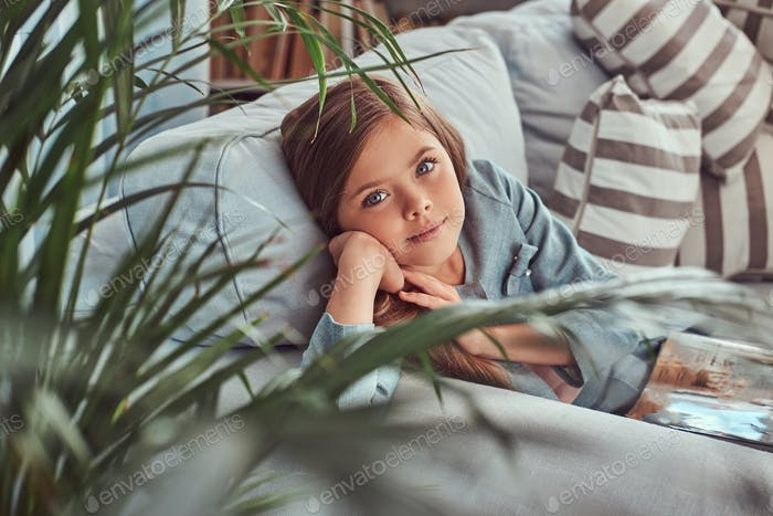 Cute little girl with long brown hair lying on a sofa at home alone