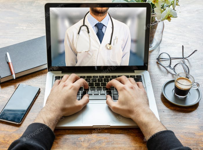 Telemedicine concept. Doctor GP on a computer screen, office desk background