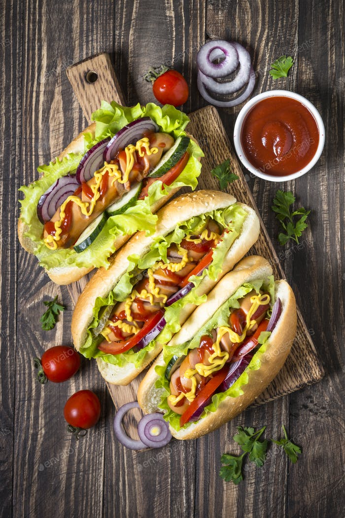 Hot dog with fresh vegetables on dark wooden table