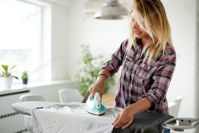 Lächelnd junge glückliche Frau Bügeln Kleidung zu Hause