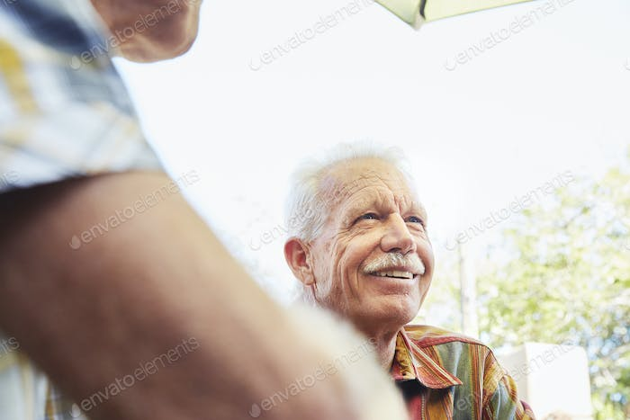 Smiling senior man with moustache sitting outdoor in company.