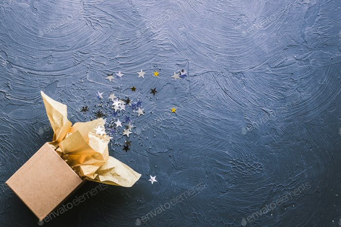 Offene Geschenkbox mit Sternen auf schwarzem Hintergrund.