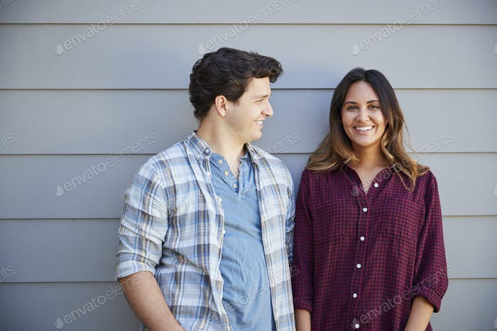 Portrait Of Couple Standing Outside Grey Clapboard House