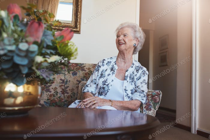 Senior woman sitting on a sofa at old age home