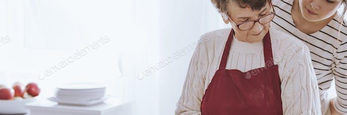 Grandmother preparing food with granddaughter