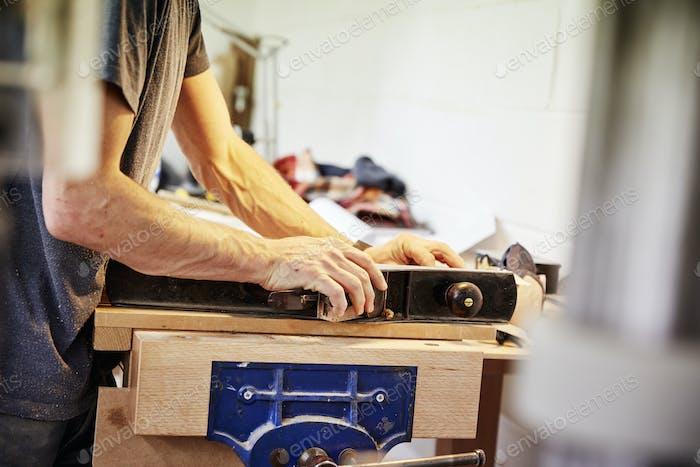 Un hombre sosteniendo un pedazo de madera en un taller de muebles haciendo muebles contemporáneos a medida.