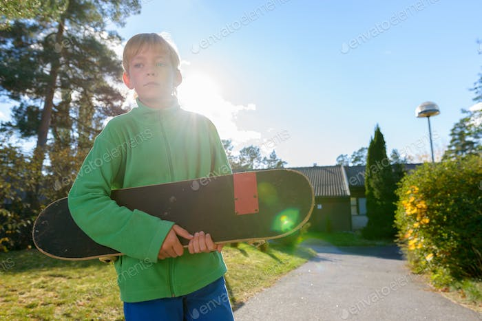 Young handsome boy thinking while holding skateboard in the front yard