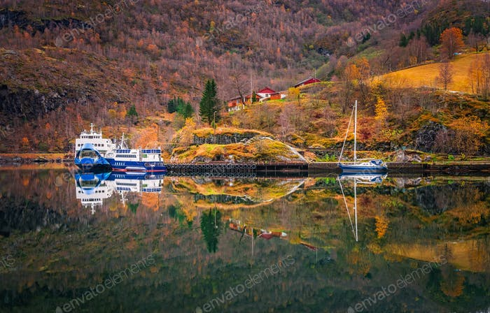 Ferry and boat anchored on the fjord shore in Flam