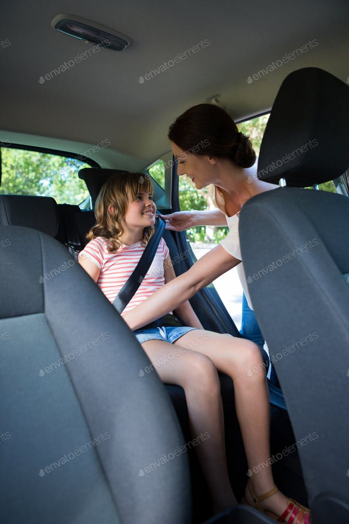 Mother securing her daughter with seat belt