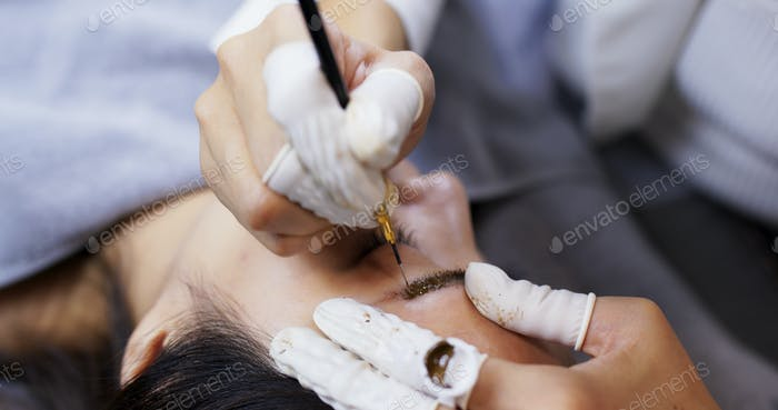 Asian woman having microblading eyebrows in a beauty salon