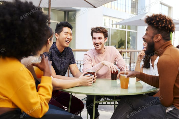 Six trendy millennial friends drinking cold brews and talking, sitting in the street outside a cafe